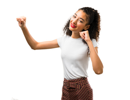 Young girl with curly hair celebrating a victory and surprised to be successful on white background