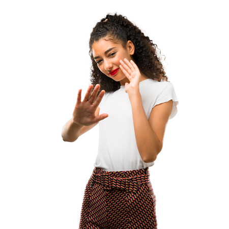 Young girl with curly hair is a little bit nervous and scared stretching hands to the front on white background