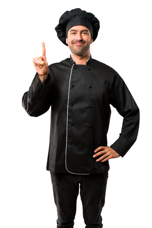 Chef man In black uniform showing and lifting a finger in sign of the best on isolated white background