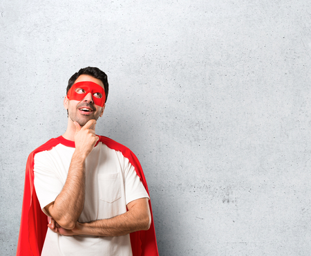 Superhero man with mask and red cape standing and thinking an idea on textured grey background