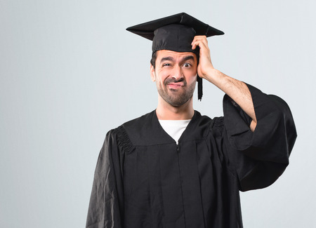 Man on his graduation day University with an expression of frustration and not understanding. Confused gesturing on grey background