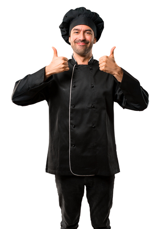 Chef man In black uniform giving a thumbs up gesture and smiling because has had success on isolated white background Zdjęcie Seryjne