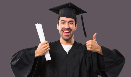Man on his graduation day University giving a thumbs up gesture and smiling because has had success on violet background 免版税图像