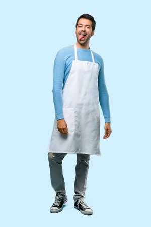 Full body of Man wearing an apron makes funny and crazy face emotion on blue background