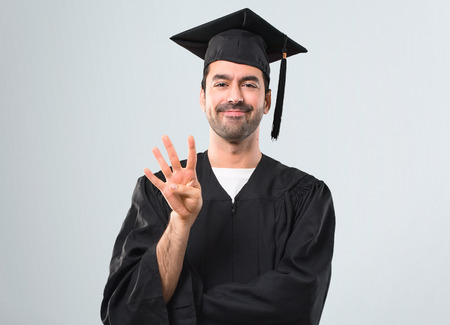 Man on his graduation day University happy and counting four with fingers on grey background