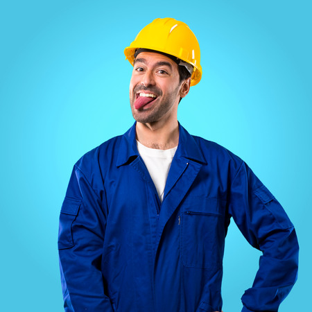 Young workman with helmet showing tongue at the camera having funny look on blue background