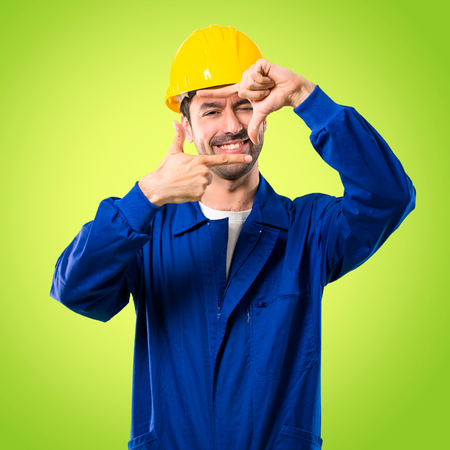 Young workman with helmet focusing face. Framing symbol on green background Stockfoto