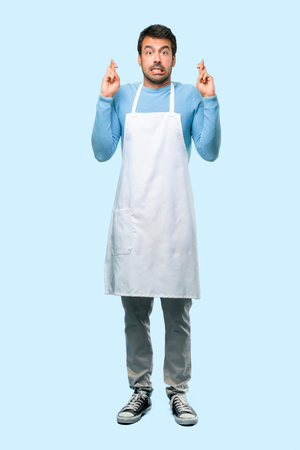 Full body of Man wearing an apron with fingers crossing and wishing the best. Making a wish. on blue background 写真素材