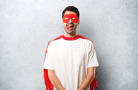 Superhero man with mask and red cape makes funny and crazy face emotion on textured grey background