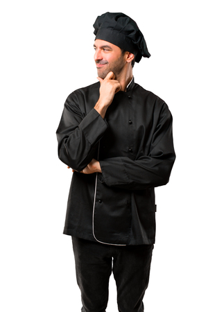 Chef man In black uniform standing and looking to the side with the hand on the chin on isolated white background