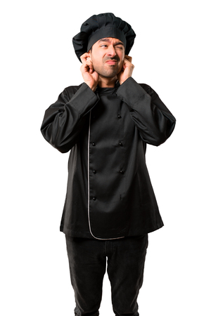 Chef man In black uniform covering both ears with hands. Frustrated expression on isolated white background Stock Photo