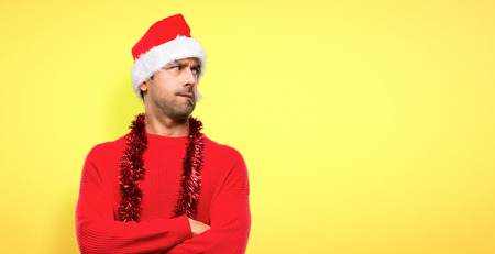 Man with red clothes celebrating the Christmas holidays with confuse face expression while bites lip on yellow background