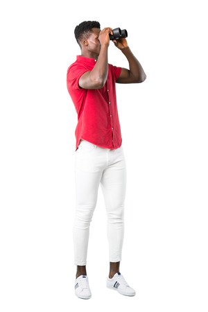 Full body of Young african american man and looking for something in the distance with binoculars on white background Imagens