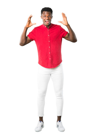 Full body of Young african american man with surprise and shocked facial expression. Gaping because can not believe what is happening on white background Stok Fotoğraf