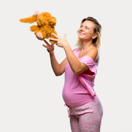 Pregnant woman in pajamas with stuffed animal on isolated grey background