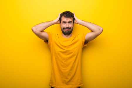 Man on isolated vibrant yellow color takes hands on head because has migraine Reklamní fotografie