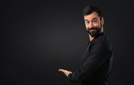 Handsome man with beard presenting something on black background