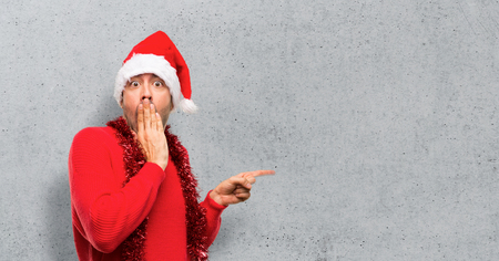 Man with red clothes celebrating the Christmas holidays pointing finger to the side with a surprised face on textured background Stock Photo