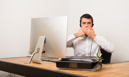 Telemarketer man in a office covering mouth with hands for saying something inappropriate
