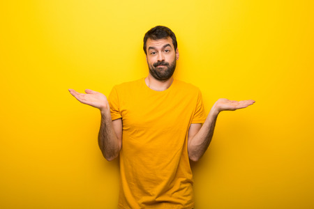 Man on isolated vibrant yellow color having doubts while raising hands and shoulders