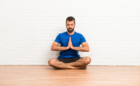 Man doing yoga exercises indoors