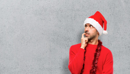 Man with red clothes celebrating the Christmas holidays having doubts while looking up on textured background Stock Photo