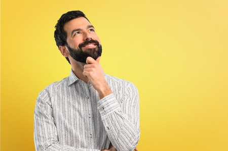 Handsome man with beard standing and thinking an idea
