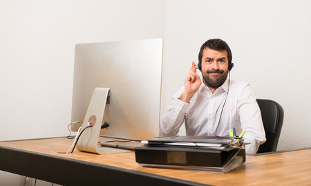 Telemarketer man in a office with fingers crossing and wishing the best