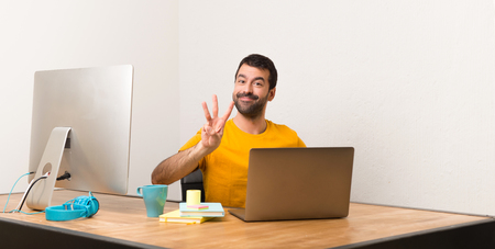 Man working with laptot in a office happy and counting three with fingers