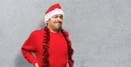 Man with red clothes celebrating the Christmas holidays suffering from backache for having made an effort on textured background