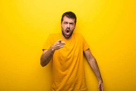 Man on isolated vibrant yellow color frustrated by a bad situation and pointing to the front Stock Photo