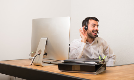 Telemarketer man in a office listening to something by putting hand on the ear