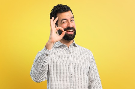 Handsome man with beard showing an ok sign with fingers