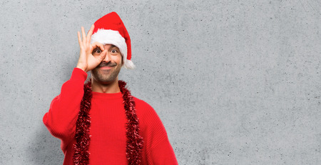 Man with red clothes celebrating the Christmas holidays makes funny and crazy face emotion on textured background