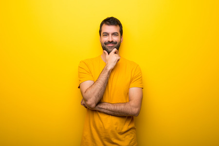 Man on isolated vibrant yellow color smiling and looking to the front with confident face Stock Photo