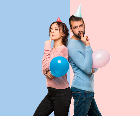 couple with balloons and birthday hats showing a sign of closing mouth and silence gesture on pink and blue background Stock Photo
