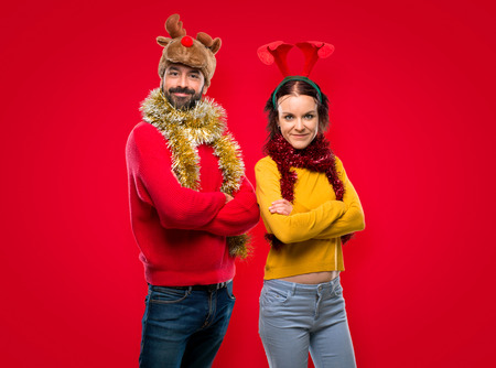 Couple dressed up for the christmas holidays keeping the arms crossed in lateral position while smiling on isolated red background Banco de Imagens