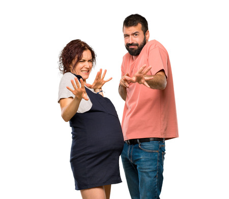 Couple with pregnant woman is a little bit nervous and scared stretching hands to the front on isolated white background Foto de archivo