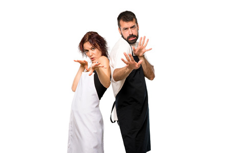 Couple of cooks is a little bit nervous and scared stretching hands to the front on isolated white background