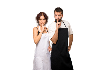 Couple of cooks showing a sign of silence gesture putting finger in mouth on isolated white background