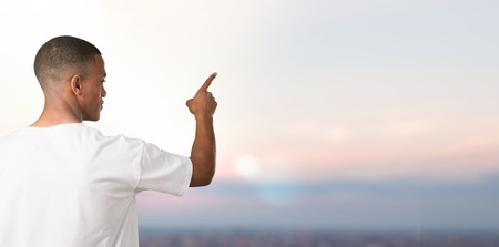 Young african american man pointing back with the index finger on sunset background