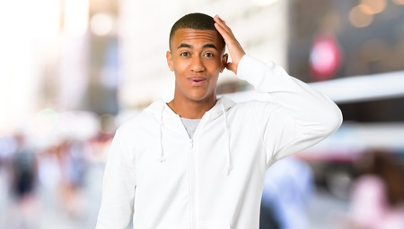 Dark-skinned young man with white sweatshirt enjoy dancing while listening to music at a party in outdoor