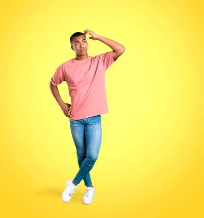 Standing young african american man having doubts and with confuse face expression while scratching head on colorful background