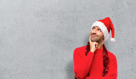 Man with red clothes celebrating the Christmas holidays standing and thinking an idea while looking up on textured background Stock Photo