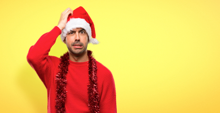Man with red clothes celebrating the Christmas holidays with an expression of frustration and not understanding on yellow background