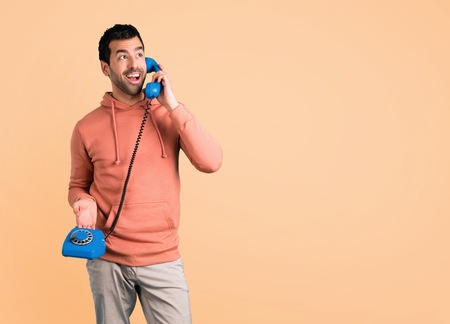 Man in a pink sweatshirt talking to vintage phone on ocher background