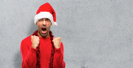 Man with red clothes celebrating the Christmas holidays frustrated by a bad situation on textured background Stock Photo
