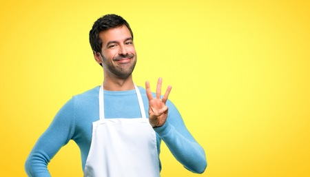 Man wearing an apron happy and counting three with fingers on yellow background Stock Photo