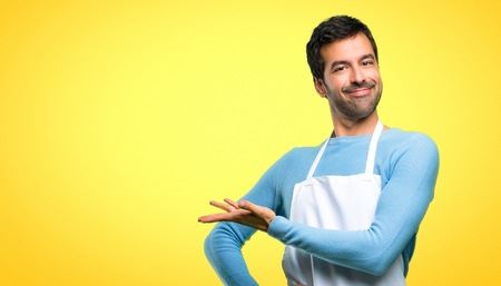 Man wearing an apron presenting a product or an idea while looking smiling towards on yellow background