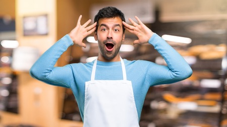 Man wearing an apron with surprise and shocked facial expression. Gaping because can not believe what is happening in a bakery